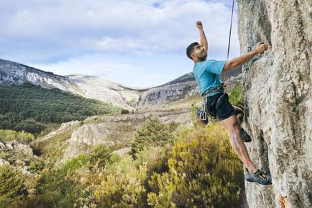 Photographie d'un homme en train d'escalader une montagne